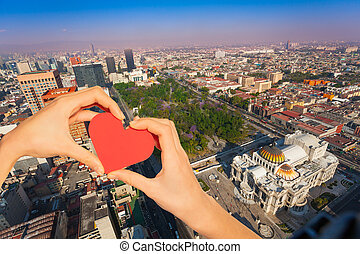 Hand hold red heart, central Alameda park, Mexico