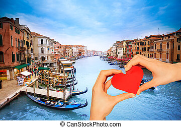 Hand hold red heart over Grande canal in Venice