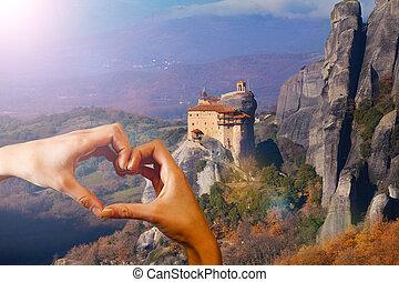 Hand hold red heart over Monastiraki monastery - Red love...