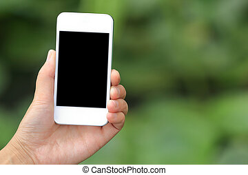 hand hold smart phone against green grass