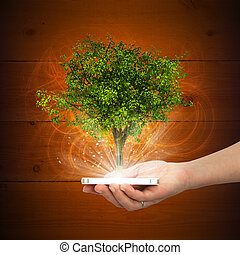 Hand hold smart phone with magical green tree