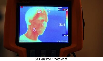 Hand hold thermal image camera, on-screen human face, hand, man opens mouth