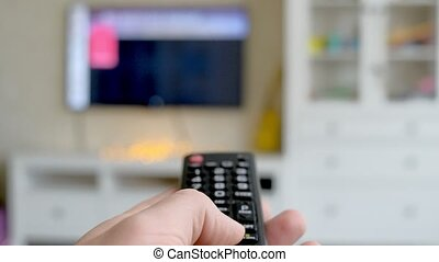 Hand hold TV remote control. TV on the background. 4k