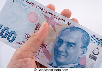 Hand holding 100 Turksh Lira banknotes  on white background