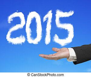 Hand holding 2015 shape cloud with blue sky