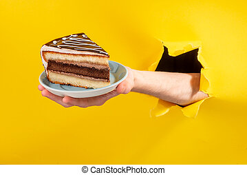 Hand holding a big piece of chocolate cake through a torn hole in yellow paper