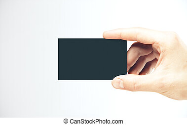 Hand holding a blank black business card.