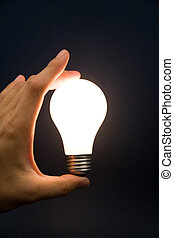 Hand holding a Bright Light Bulb, Concept of Inspiration,...