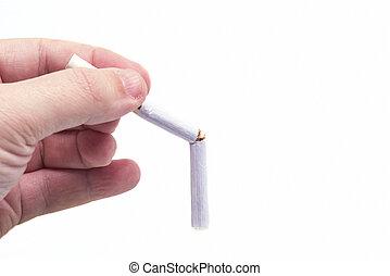 Hand holding a broken cigarette