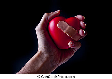 Hand Holding a Broken Heart - A hand holding a heart with a...