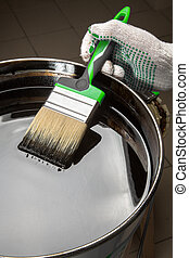 hand holding a brush on can with black mastic