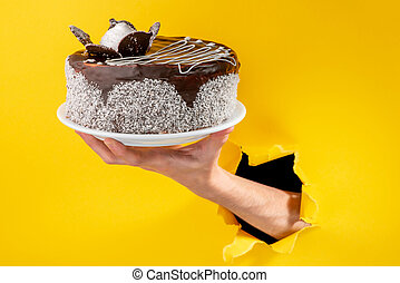 Hand holding a chocolate cake through a torn hole in yellow paper backgroun