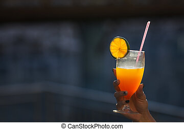 hand holding a cocktail with an orange in glass outdoor