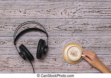 Hand holding a coffee Cup and black wired headphones on the wooden table.