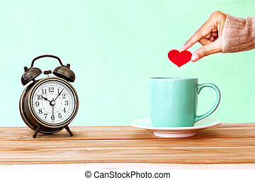 hand holding a Coffee cup mug on wooden table , Romance and love background . Happy and relax concept