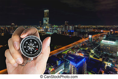 Hand holding a Compass in for direction complication urban city concept