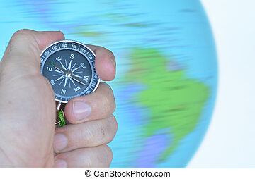Hand holding a compass with a spinning globe