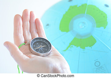 Hand holding a compass with Antarctica on a globe