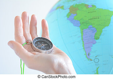 Hand holding a compass with South America on a globe