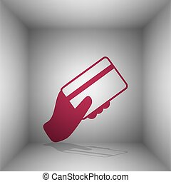 Hand holding a credit card. Bordo icon with shadow in the room.