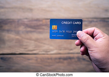 Hand holding a credit card make purchases online and conduct financial transactions.