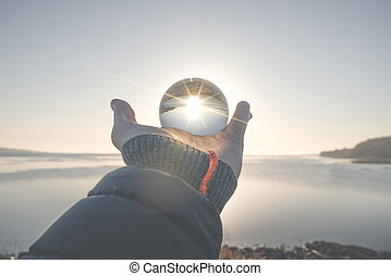 Hand holding a crystal ball in the winter sunrise