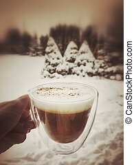 hand holding a cup of coffee against garden under snow
