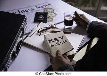 Hand holding a cup of coffee and reading a book key of success - concept lifestyle
