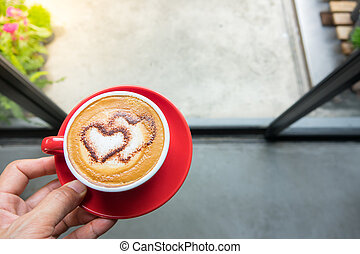 Hand holding a cup of coffee in coffee shop
