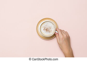Hand holding a Cup of coffee with cream and cinnamon on a coral background.