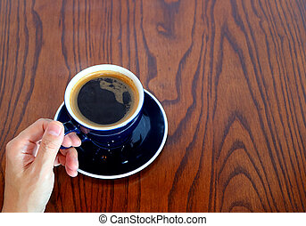 Hand holding a cup of hot coffee on the wooden table