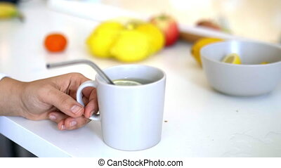 Hand holding cup of lemon tea with straw and lemon slice floating inside. Lemon-flavored drink in cup with lemons on table as background. Sweet citric beverages