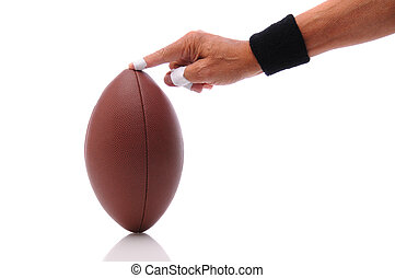 Hand holding a football ready for kicking