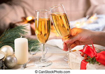 Hand holding a glass of champagne on a Christmas background.