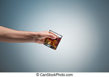 Hand holding a glass of whiskey