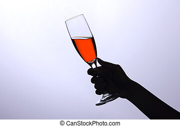 Hand holding a glass with wine