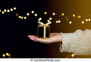 hand holding a gold gift box with gold ribbon,bokeh sparkle background, Christmas or Birthday present concept with space for text