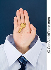 Hand holding a golden key