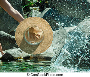 Hand holding a hat on the water