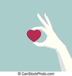 Hand holding a heart symbol on the blue background