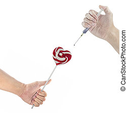 Hand holding a lollipop and using syringe