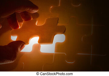 Hand holding a missing jigsaw puzzle piece with light glow