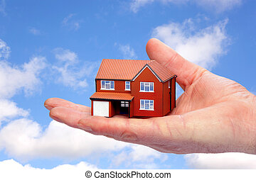 Hand holding a model home against sky background. - Photo of...