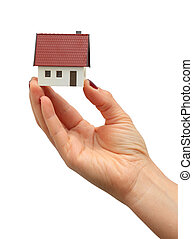 Hand holding a new house isolated over white background