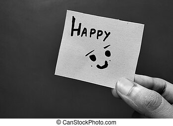 Hand holding a paper card with the word HAPPY