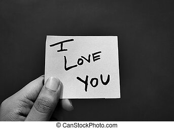 Hand holding a paper card with the words I LOVE YOU
