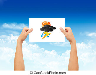 Hand holding a paper with weather sign on landscape blue sky background
