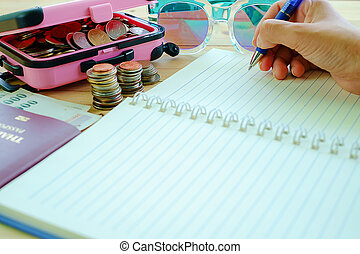 Hand holding a pen to write on the blank notebook with stack of coins in pink luggage, Thai banknotes currency, passport and fashion sunglasses