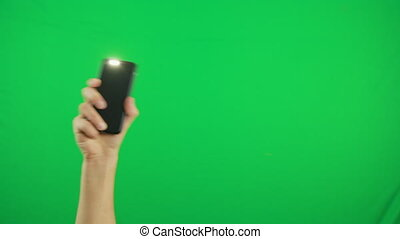 Hand holding a phone with a green screen on it over a blue background. Close up footage of hand only
