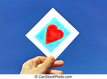 Hand holding a picture of a heart against the blue sky